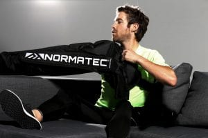 man putting on normatec arm attachment