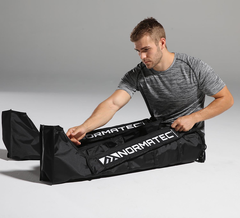 man adjusting normatec leg attachments